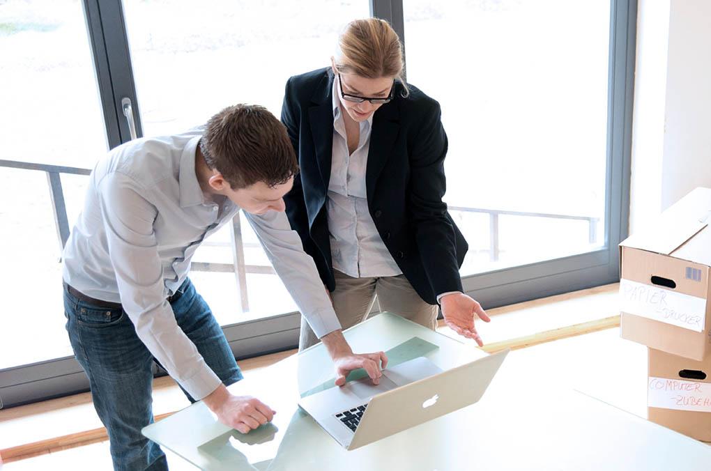Existengründung, Startup, Start-Up, Existenzgründer in Ihrem neuen Büro mit Schreibtisch, Computer und Umzugskartons.