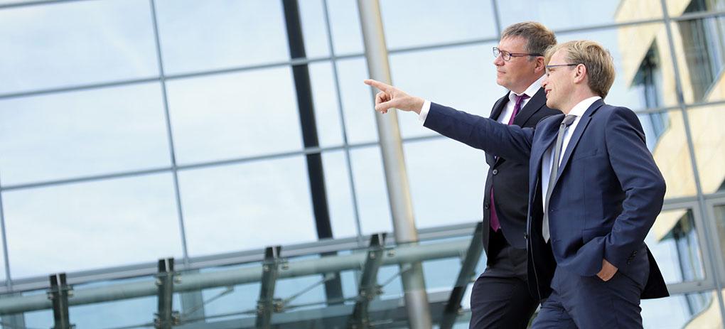 Teamfoto, Mitarbeiter bzw. Führungskräfte im Gespräch vor der Glasfassade ihres Unternehmens.