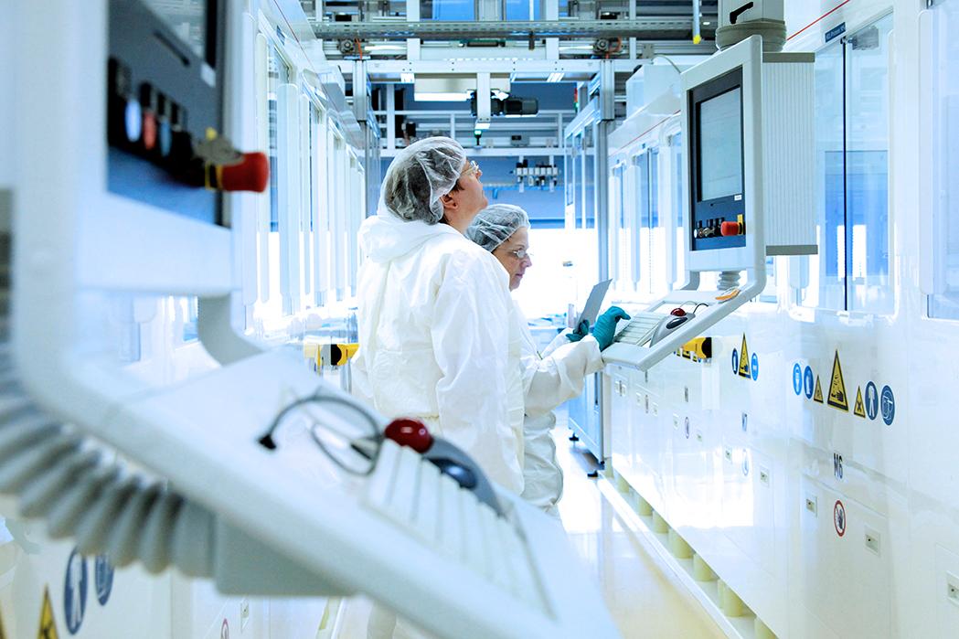 Produktion Photovoltaik-Anlagen: Technikerinnen kontrollieren die Produktion von Solarzellen in einer vollautomatisierten Produktions-Straße für Photovoltaik-Module. Freiberg, Sachsen, Germany