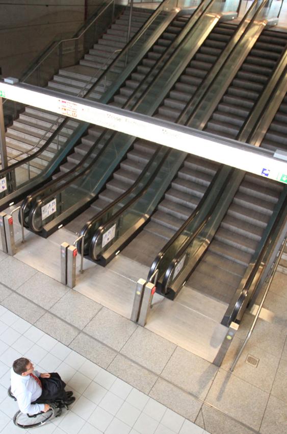 Barrierefreiheit im öffentlichen Raum: Aufnahme einer Rolltreppenanlage in einem U-Bahnhof in Frankfurt. Perspektive von oben auf Bahnsteig, Rolltreppen und Treppen. Ein Rollstuhlfahrer steht vor den Treppen. Stadt Frankfurt am Main, Hessen, reportage_foto_frankfurt_barrierefreiheit_klewar-photographie